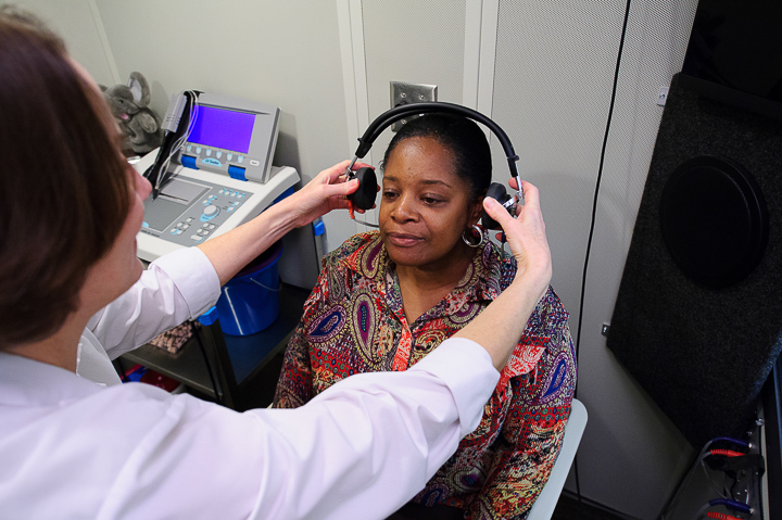 Audiologist places headphones for hearing test